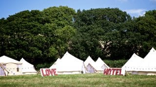 Sandstone Glamping Tents with 'Love Hotel' Sign